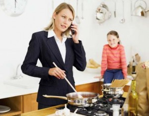 mother talking on a mobile phone while cooking with her daughter